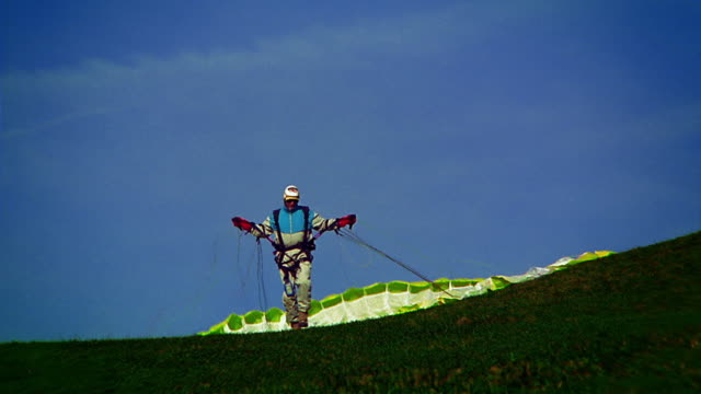 vidéos et rushes de medium shot man in parachute harness on top of mountain walks forward for take off / tyrol, austria - parapente