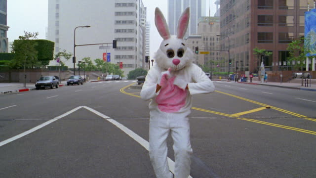 medium shot man in rabbit costume break dancing in street / los angeles, ca - tipo di danza video stock e b–roll