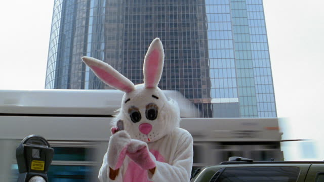 Medium shot man in rabbit costume dialing telephone number and listening to cell phone with office building in background