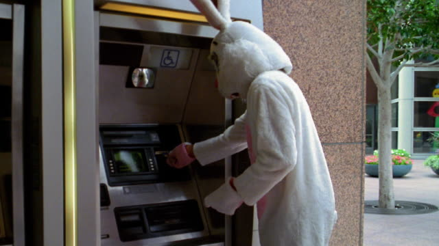 medium shot man in rabbit costume looking around corner / inserting and retrieving card from atm machine - kelly mason videos stock-videos und b-roll-filmmaterial