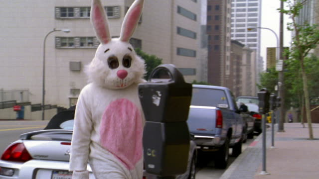 medium shot man in rabbit costume moving away from car and placing coin into parking meter / los angeles, ca - rabbit costume stock videos & royalty-free footage