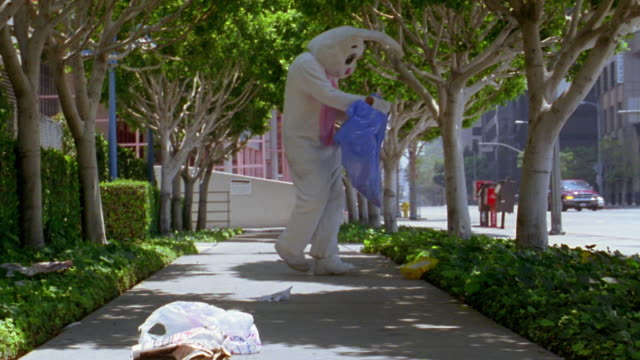 medium shot man in rabbit costume picking up litter and depositing in garbage bag along city walkway / l.a. - dustman stock videos & royalty-free footage