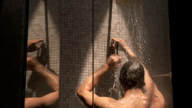 vídeos de stock e filmes b-roll de medium shot man in shower - casa de banho