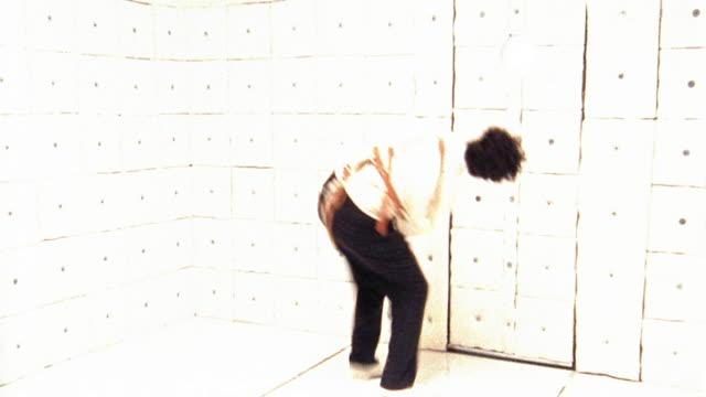 Medium shot man in straitjacket making faces and running around padded room (flash frames)