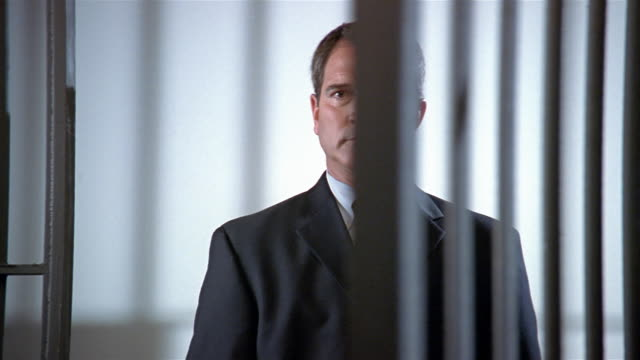 Medium shot man in suit against white background looking at camera/ prison door closes on him/ man holding prison bars, looking angry