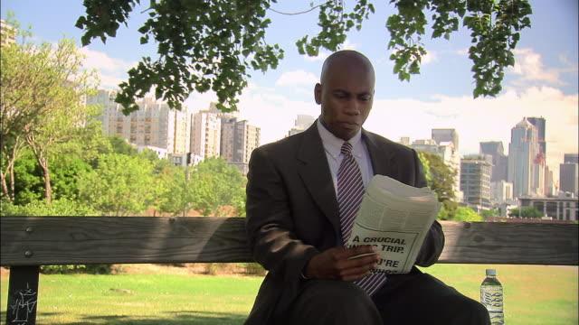 vidéos et rushes de medium shot man in suit eating lunch on bench under tree in myrtle edwards park / seattle - complètement chauve