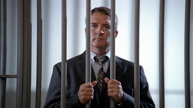 medium shot man in suit in prison holding onto bars and looking at camera/ man looking down - prison bars stock videos and b-roll footage