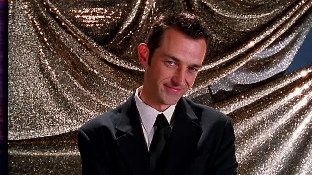 Medium shot man in suit posing / silver backdrop in background