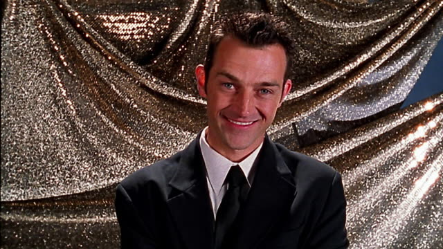 Medium shot man in suit smiling / walking away / silver backdrop in background