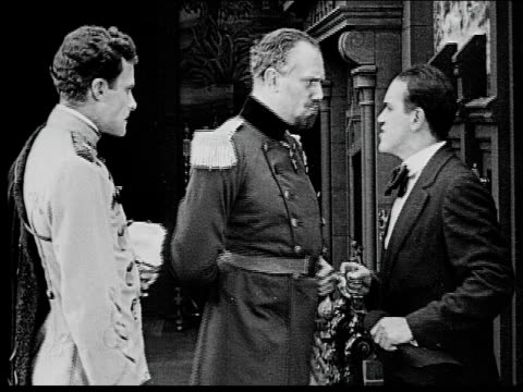 1916 b/w medium shot man in suit talking to two grave-looking men in military uniforms - anno 1916 video stock e b–roll