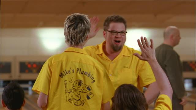 medium shot man in team jersey smiling and slapping hands w/teammates - freizeitaktivität stock-videos und b-roll-filmmaterial