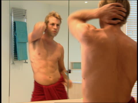 Medium shot man in towel dancing and looking in bathroom mirror