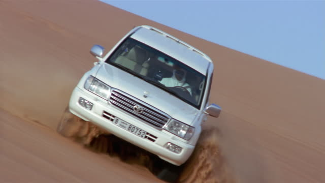 stockvideo's en b-roll-footage met medium shot man in traditional middle eastern clothing driving toyota suv down sand dune/ dubai - toyota motor