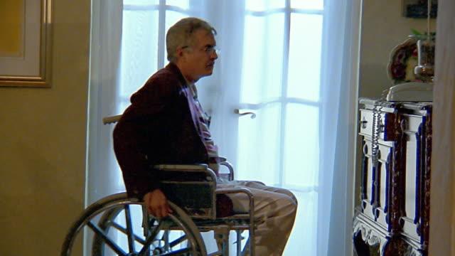 medium shot man in wheelchair answering telephone - 50 59 years stock videos & royalty-free footage