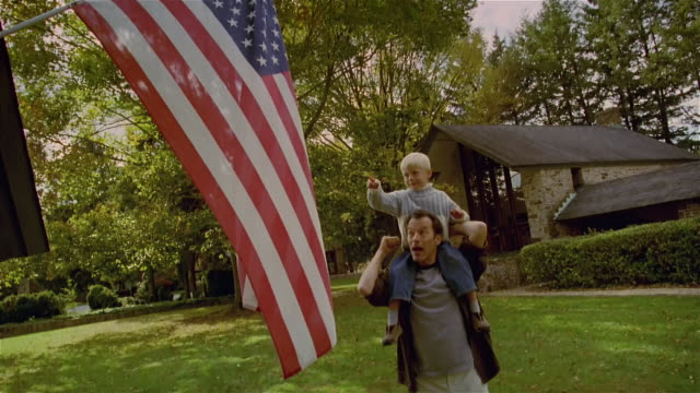Medium shot man in yard with boy on shoulder pointing at US flag and counting/ Solebury, Pennsylvania