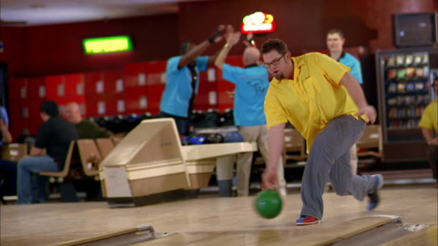 vídeos de stock, filmes e b-roll de medium shot man in yellow team jersey bowling and cheering w/teammates - cancha de jogo de boliche