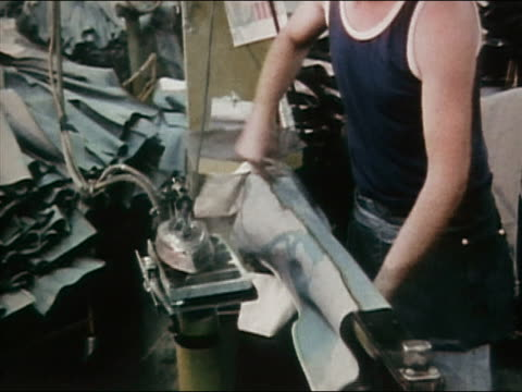 1980 medium shot man ironing denim jeans at jeans factory / AUDIO