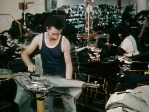 vídeos de stock e filmes b-roll de 1980 medium shot man ironing jeans at jeans factory / women sewing in background / audio - jeans