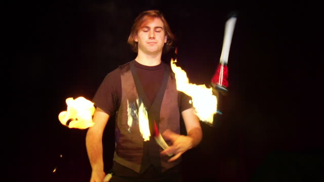 medium shot man juggling flaming torches turning to face camera - juggler stock videos and b-roll footage