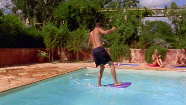 medium shot man jumping on raft in pool and trying to surf / falling in pool / sunbathers near pool clapping - one teenage boy only stock videos & royalty-free footage