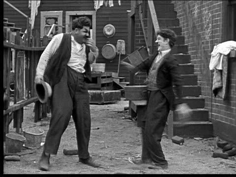 1918 b/w medium shot man kicking other man in stomach as they both laugh/ man putting barrel between them/ other man kicking barrel over - oliver hardy stock videos & royalty-free footage