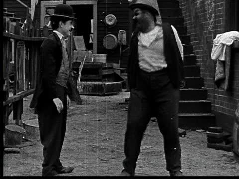 1918 b/w medium shot man kicking other man/ men both dance around/ one man picking up bricks - oliver hardy stock videos & royalty-free footage