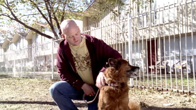 Medium shot man kneeling on sidewalk and petting dog on autumn day