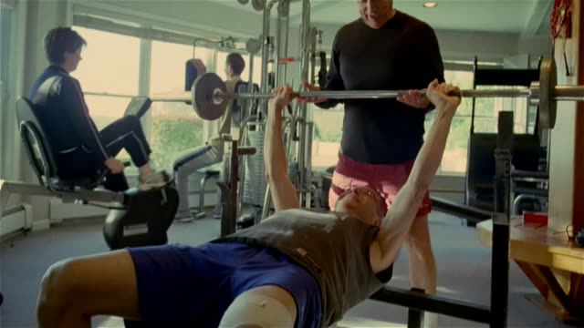 medium shot man lifting weights on weight bench with other man spotting him/ solebury, pennsylvania - strength training stock videos & royalty-free footage