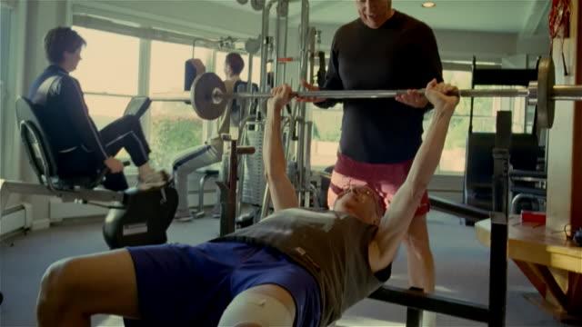 vidéos et rushes de medium shot man lifting weights on weight bench with other man spotting him/ solebury, pennsylvania - musclé