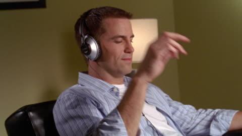 vídeos y material grabado en eventos de stock de medium shot man listening to music with headphones - ojos cerrados