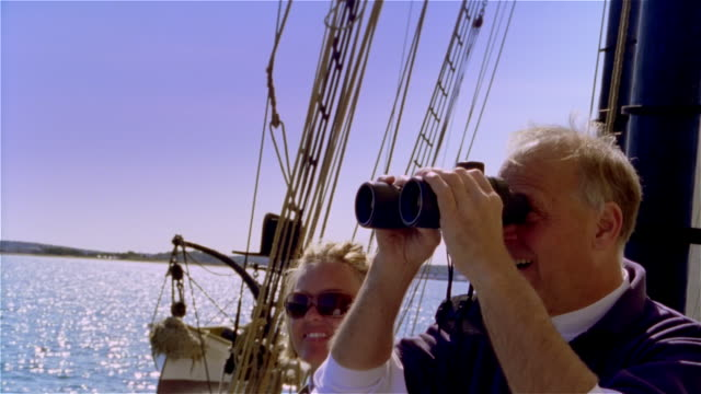 medium shot man looking at view from ship with binoculars / woman wearing sunglasses standing next to him - whale watching stock videos and b-roll footage