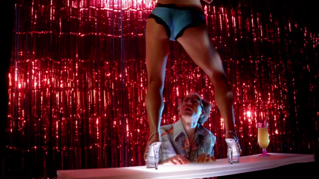 vidéos et rushes de medium shot man looking up at female stripper on stage / throwing bikini over his face - peep show