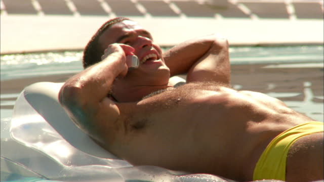 vídeos y material grabado en eventos de stock de medium shot man lying on raft and talking on telephone in swimming pool - vello pectoral