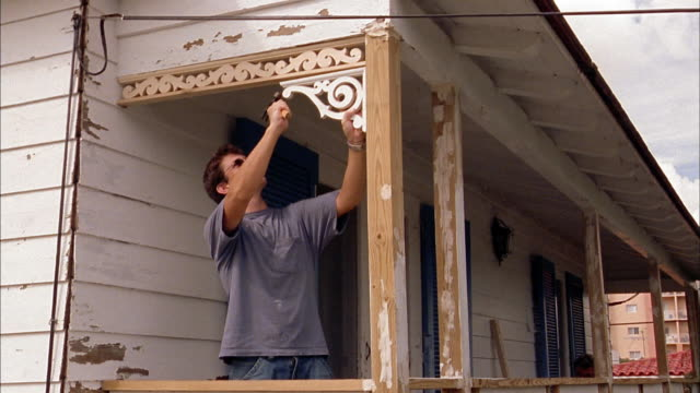 medium shot man nailing molding into porch - hammer stock videos & royalty-free footage