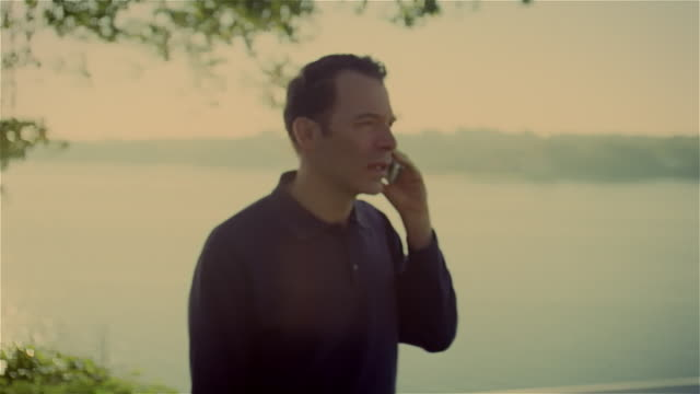 medium shot man on deck talking on cordless phone - schnurloses telefon stock-videos und b-roll-filmmaterial
