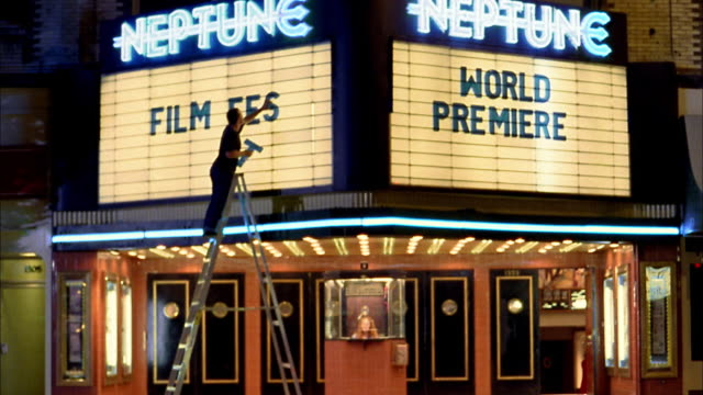 Medium shot man on ladder placing letters on movie theater marquee / Seattle, Washington