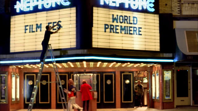 medium shot man on ladder placing letters on movie theater marquee / people leaving theater / seattle - film premiere stock videos & royalty-free footage