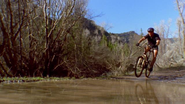 medium shot man on mountain bike riding through muddy water w/mountains and trees in background / colorado - mountain biking stock videos & royalty-free footage