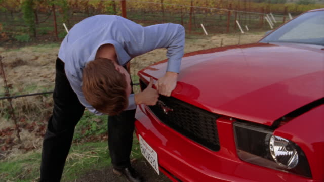 medium shot man opening hood on red convertible on country roadside/ napa valley, california - ford mustang stock videos and b-roll footage