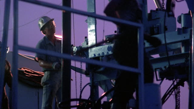 Medium shot man operating machine on oil rig / Texas