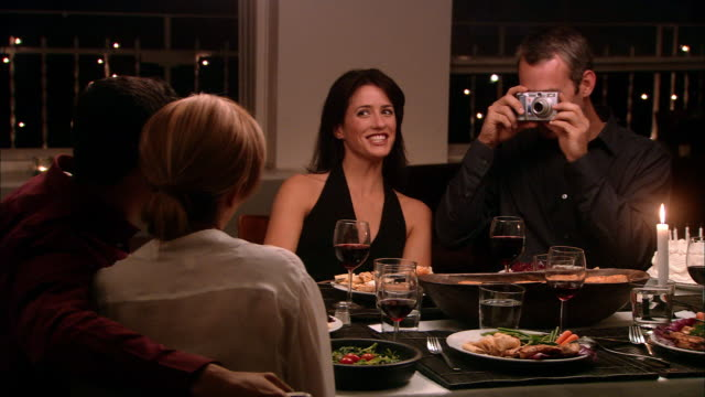 Medium shot man photographing couple at dinner party as other woman watches