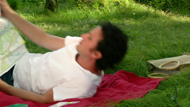 medium shot man picking up hiking map and lying on back in grass to read it - lying on back stock videos & royalty-free footage