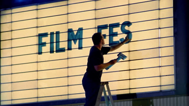 Medium shot man placing letters on movie theater marquee / Seattle, Washington