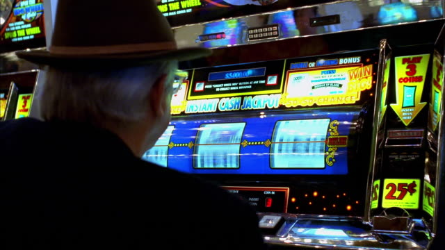 vídeos y material grabado en eventos de stock de medium shot man playing slot machine and hitting jackpot in las vegas casino - tragaperras