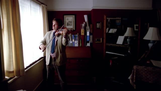 medium shot man playing violin near window - violin stock videos & royalty-free footage
