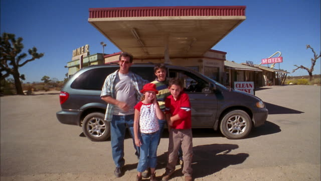 Medium shot man posing with children in front of van parked at gas station