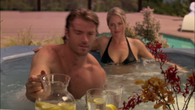medium shot man pouring glasses of lemonade while sitting in hot tub/ man and woman leaning back in tub/ monterey county, california - beccuccio video stock e b–roll