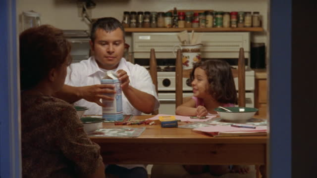 vidéos et rushes de medium shot man pouring milk and cereal for wife and daughter at breakfast table/ man drawing with daughter/ california - brique