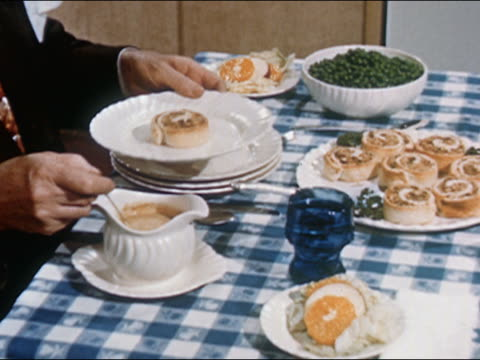 1951 Medium shot man prepares plate with pastry, gravy, and peas / AUDIO