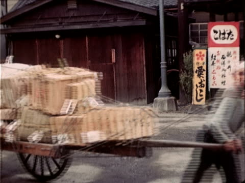 1939 medium shot man pulling cart loaded with boxes/ japan - cart stock videos & royalty-free footage